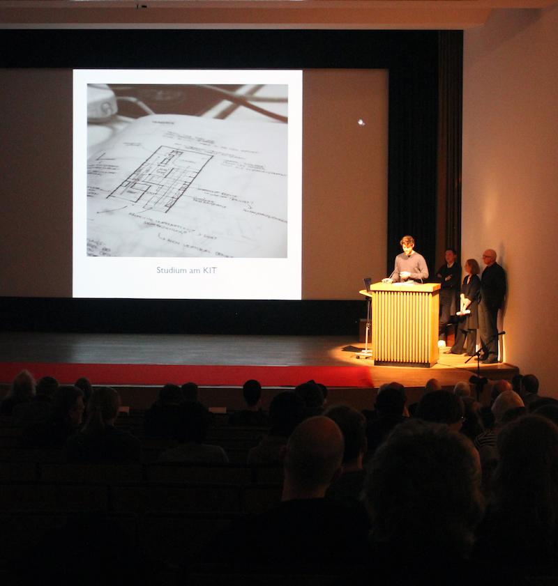 Der Studierende Christian Schramm am Podium des Saals im Japanischen Kulturinstitut