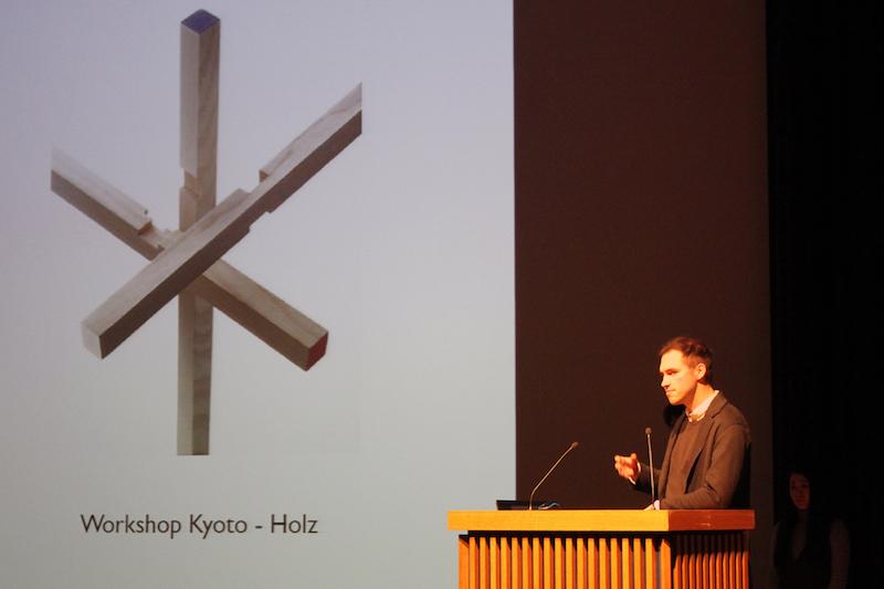 Der Studierende Fabian Reckers am Podium des Saals im Japanischen Kulturinstitut