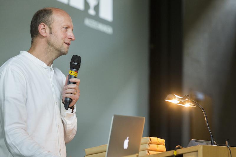Vertretungsprofessor Christopher Schroeer-Heiermann auf der Bühne des Karl-Schüssler-Saals