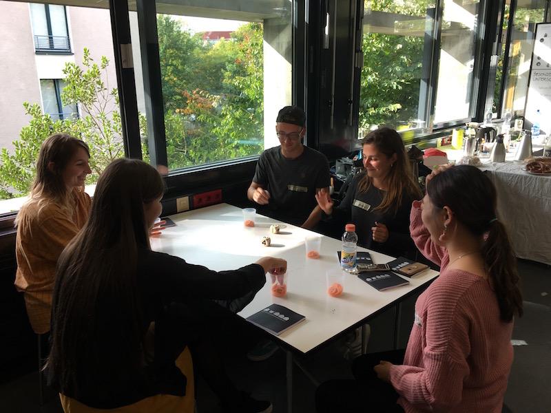 Austauschstudierende sitzen um einen Tisch